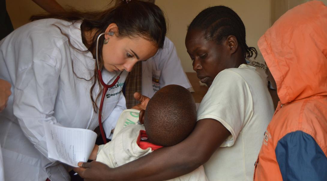 A Projects Abroad volunteer doing a midwifery internship in Ghana checks a baby's stomach.